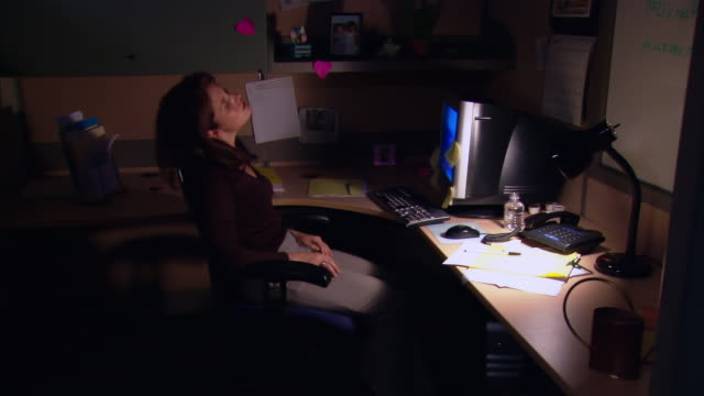 medium shot dolly shot tired woman working late in cubicle / stretching - young women stock videos & royalty-free footage
