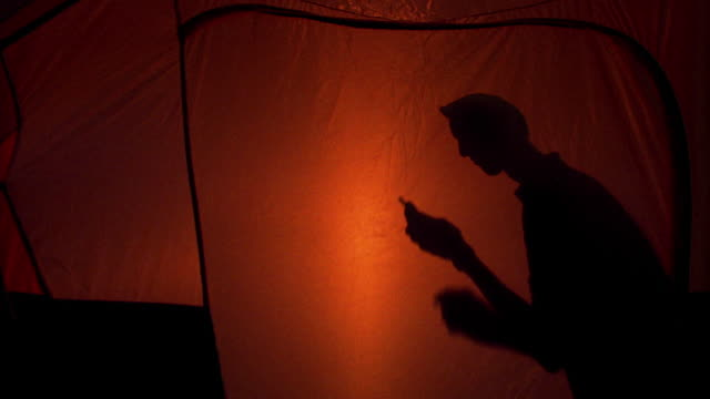 stockvideo's en b-roll-footage met medium shot dolly shot to wide shot silhoutted man dialing and talking on cell phone in tent at twilight / utah - tent