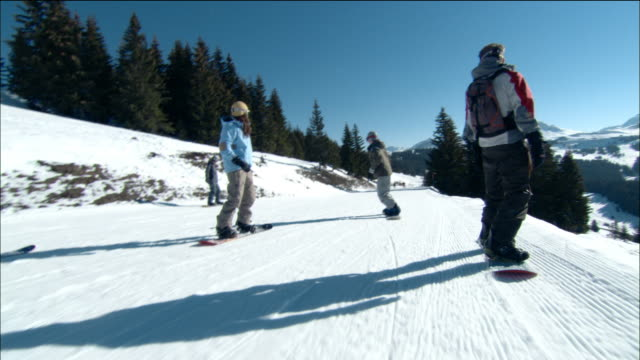medium shot dolly shot tracking shot man snowboarding downhill with others / morzine, france - mitten stock videos & royalty-free footage