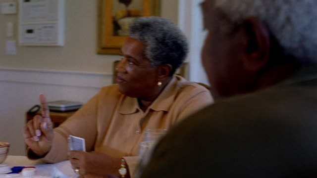 medium shot dolly shot two senior black couples laughing while playing cards around table with glasses of lemonade - playing card stock videos & royalty-free footage