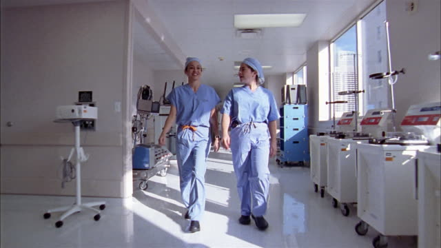 Medium shot dolly shot two women wearing scrubs walking down hall in hospital / medical equipment in background