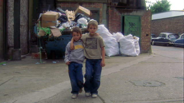 Medium shot dolly shot two young boys walking towards CAM w/arms around each other in alley w/cars and garbage in background