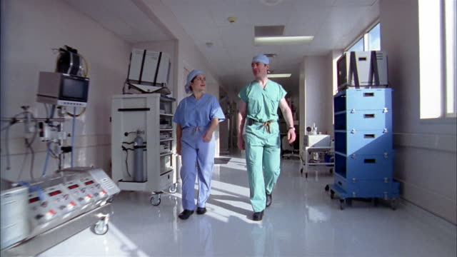 vídeos de stock e filmes b-roll de medium shot dolly shot woman and man wearing scrubs walking down hall in hospital + talking / medical equipment in background - dolly shot