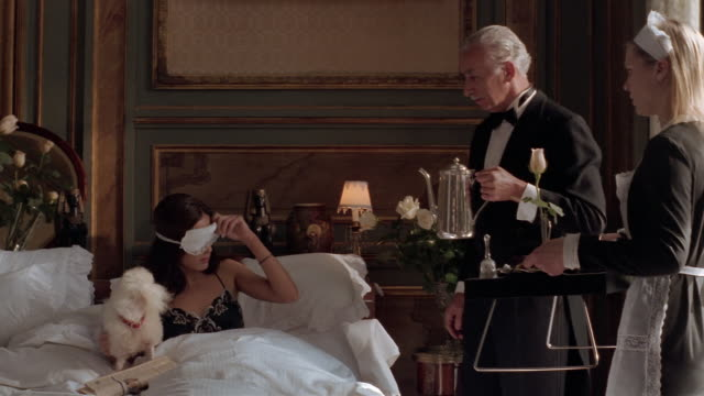 stockvideo's en b-roll-footage met medium shot dolly shot woman being served breakfast in bed by butler and maid / woman angrily waving off servants - overvloed