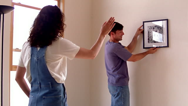 medium shot dolly shot woman directing man as he hangs picture on wall - one mid adult man only stock videos & royalty-free footage