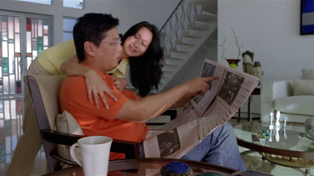 vídeos de stock, filmes e b-roll de medium shot dolly shot woman leaning over man's shoulder as he sits in living room reading newspaper / kissing him on cheek and walking away - domingo