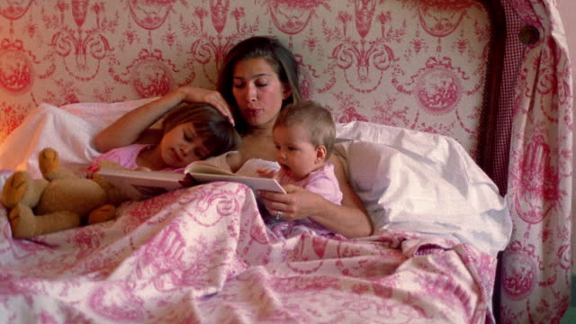 Medium shot dolly shot woman reading to young girl and baby in bed