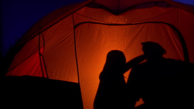 medium shot dolly shot woman yawning and hugging man in tent, couple lying down with wide shot light tuning off / utah - zelt stock-videos und b-roll-filmmaterial