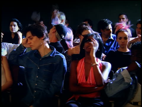 vidéos et rushes de medium shot dolly shot young adults looking bored in audience and leaving - frustration