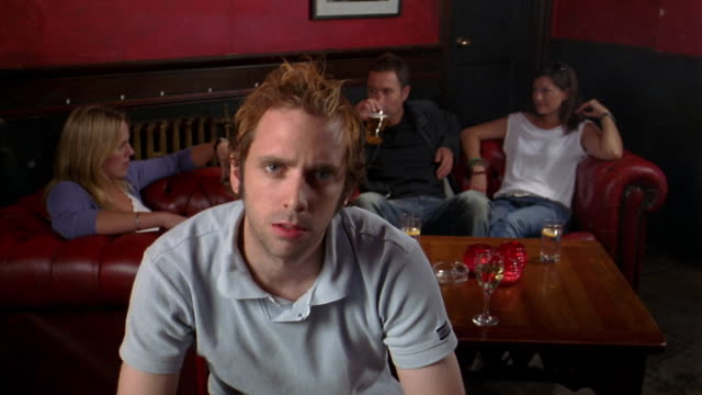 Medium shot dolly shot young man sitting in bar and looking at CAM w/group of people sitting in background on sofa drinking