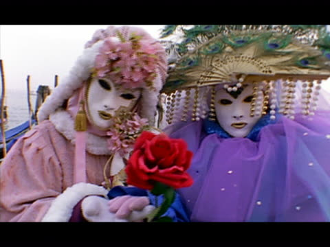 vídeos y material grabado en eventos de stock de medium shot dolly shot zoom in zoom out two people standing on pier dressed in carnivale masks and costumes ans holding flowers / venice, italy - formato buzón