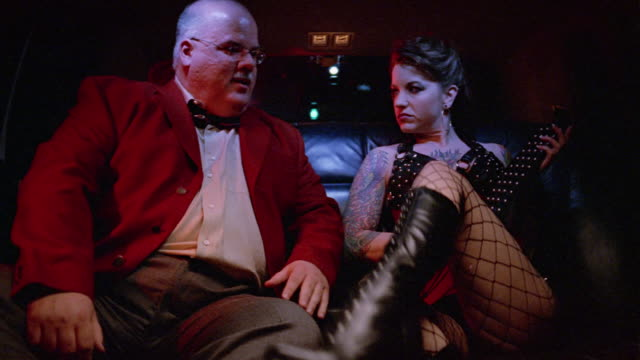 medium shot dominatrix and client riding in back of limo / client licking her boot / dominatrix smacking studded paddle against her palm - dominatrix stock videos and b-roll footage