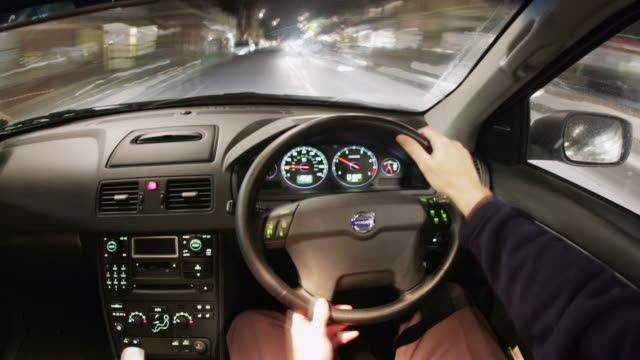 Medium shot driver's point of view nighttime city driving with right-side steering / England