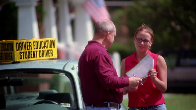 medium shot driving instructor reviewing road test results with female student driver, informing her she passed - ausbilder stock-videos und b-roll-filmmaterial