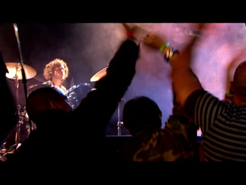 stockvideo's en b-roll-footage met medium shot drummer in band performing on stage/ zoom out crowd/ tilt up singer/ tilt down drummer/ london, england - mid volwassen mannen