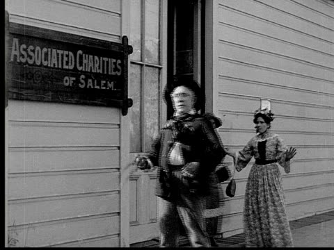 vídeos de stock, filmes e b-roll de 1913 b/w medium shot drunk old man walking past women gossiping outside associated charities building / usa  - local religioso