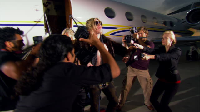 Medium shot Drunk rock star exiting private airplane with two groupies, drinking from liquor bottle and posing for paparazzi photographers at dusk / Long Beach, California, USA