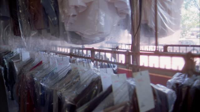 Medium shot dry cleaned garments in plastic bags moving along rack on hooks