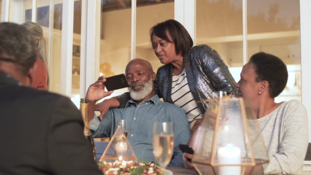 medium shot, elderly african american couple look at cellphone - photographing stock-videos und b-roll-filmmaterial