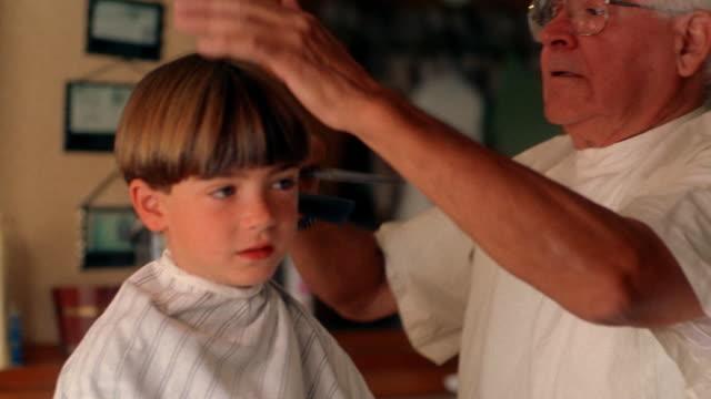 stockvideo's en b-roll-footage met medium shot elderly barber combing young boy's hair in barbershop - kammen