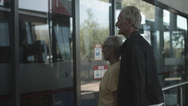vidéos et rushes de medium shot, elderly couple wait to get on bus - door
