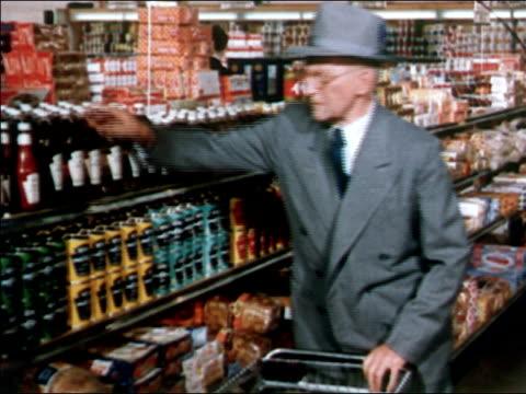 1951 Medium shot elderly man taking Heinz ketchup from supermarket shelf and placing it in grocery cart / AUDIO