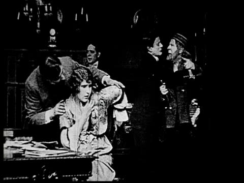 1914 b/w medium shot elderly sailor attacking wealthy woman with dagger before being restrained by businessmen  - dagger stock videos & royalty-free footage