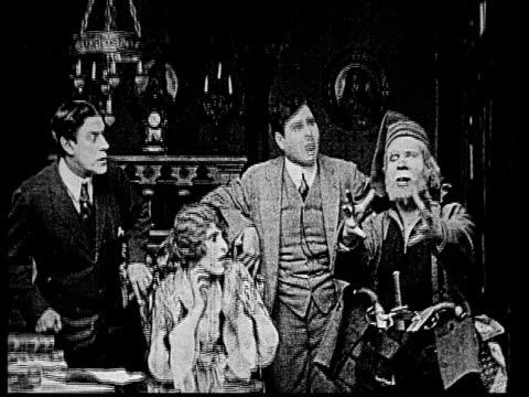 1914 b/w medium shot elderly sailor gesturing and telling story to scared woman and businessmen  - 1914年点の映像素材/bロール
