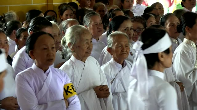 medium shot elderly women worshippers of cao dai religion attending a mass shot on january 2016 - theology stock videos and b-roll footage