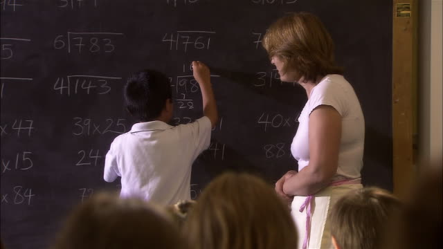 medium shot elementary school teacher helping boy solve division problem on chalk board/ boy turning to face class and smiling/ london - 2006 stock videos & royalty-free footage