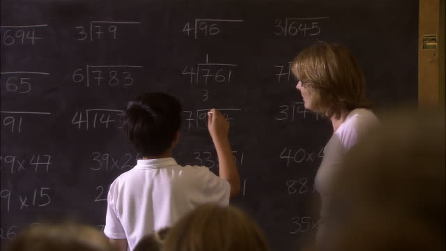 vidéos et rushes de medium shot elementary school teacher helping boy solve division problem on chalk board/ boy turning to face class and smiling/ london - tableau