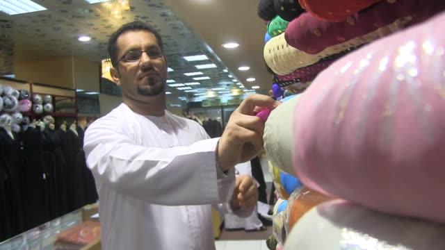 medium shot. emirati traditional clothing store in abu dhabi, united arab emirates. shot on november 2012 . - ペルシャ湾点の映像素材/bロール