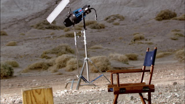 medium shot empty director's chair near electric light on desert film set / red rock canyon state park, california - electric chair stock videos & royalty-free footage