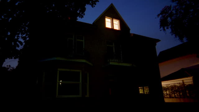 Medium shot empty house at night w/lights off / lights slowly turning on in rooms