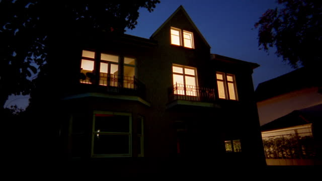 Medium shot empty house at night w/lights on / lights slowly turning off in rooms