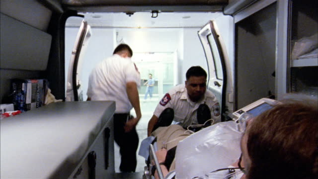 Medium shot EMTs removing patient from back of ambulance on gurney / doctors wheeling him into hospital