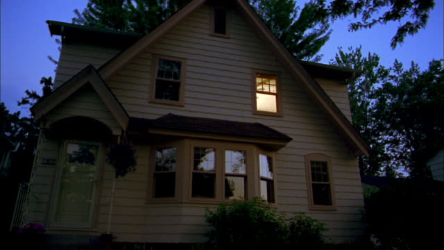 medium shot exterior view of house at dawn / lights turning on and off in rooms - house stock videos & royalty-free footage