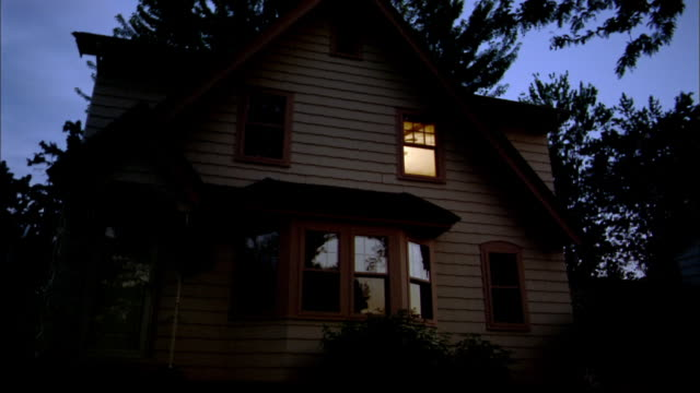 Medium shot exterior view of house at dawn / lights turning on