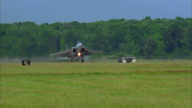 Medium shot F-15 fighter jet taking off and raising landing gear