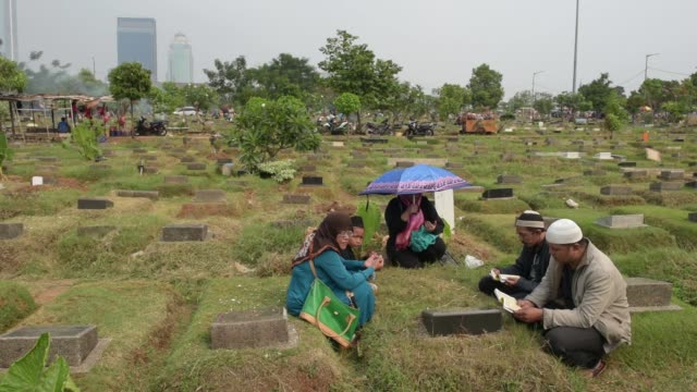 Medium shot families follow the tradition of throwing flower petals onto the graves of ancestors Wide shot families pray together at the gravesite of...