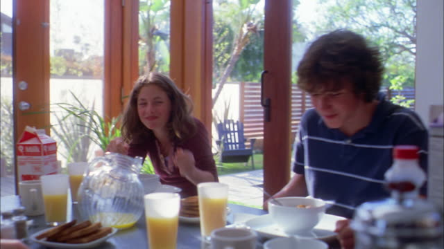 vidéos et rushes de medium shot family eating breakfast at table / brother and sister laughing - teenage girls