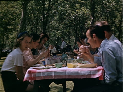 1939 medium shot family eating picnic lunch together in griffith park / los angeles, california, usa  - family reunion stock videos and b-roll footage