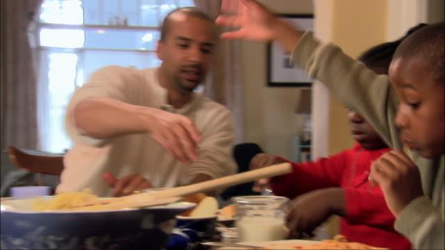Medium shot family eating spaghetti at dinner table