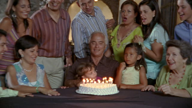 Medium shot family gathered behind table to watch grandfather blow candles on birthday cake / Mexico