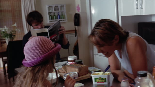 vídeos de stock, filmes e b-roll de medium shot family having breakfast / daughter buttering toast / father reading magazine - dois genitores