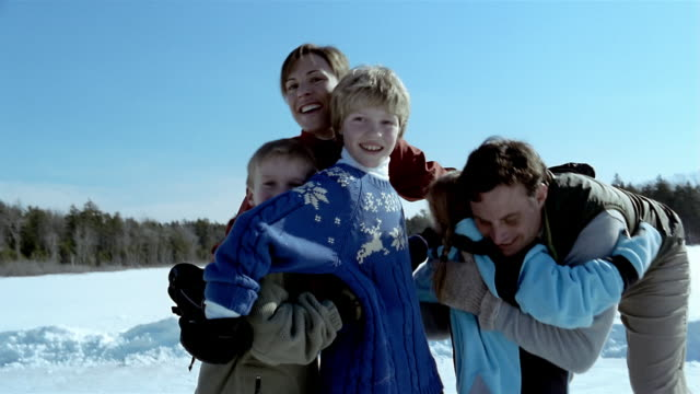 medium shot family hugging and posing for portrait on ice skates - jumper stock videos and b-roll footage