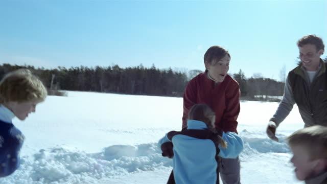 vidéos et rushes de medium shot family ice skating on frozen lake - patinage sur glace