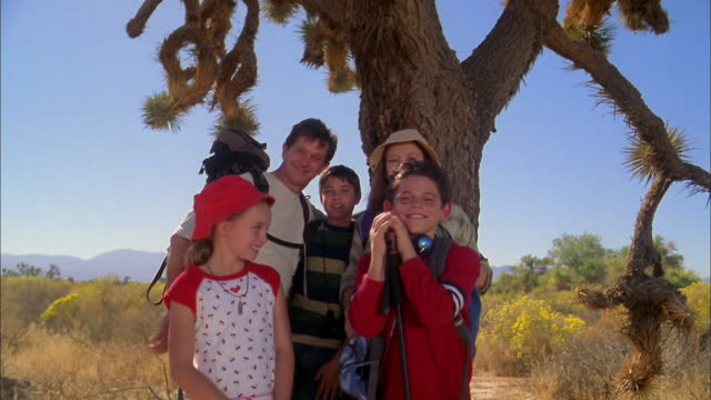 Medium shot family in hiking gear posing by desert tree and looking at CAM