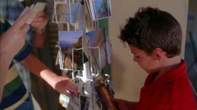 medium shot family looking at postcards on display rack in front of store - postcard stock videos & royalty-free footage