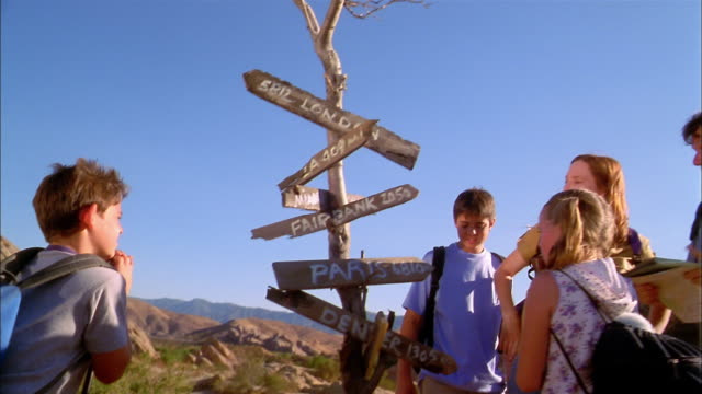 Medium shot family on hiking trip stopping at road sign w/directions to national and international cities